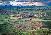 From the Absaroka Mountains in the distance to the valley floor cut with river channels, this view <br /> from Dubois, Wyoming of the Wind River Valley is not only beautiful, but captures the effect of myriad geologic processes over thousands of years. The vibrant red and white layers of the Eocene Wind River Formation have weathered into a badlands topography and the mountains in the distance are made of mid-Eocene Absaroka volcanics from millions of years ago.