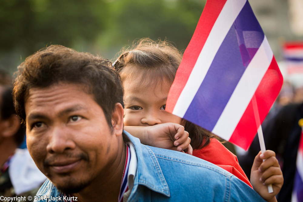 26 JANUARY 2014 - BANGKOK, THAILAND: A man and his daughter participate in an anti-government rally at Bang Kapi school in Bangkok. Anti-government protestors forced the closure of polling places in Bangkok Sunday as a part of Shutdown Bangkok. Early voting was supposed to be Sunday January 26 but blocked polling places left hundreds of thousands of people unable to vote casting the February 2 general election into doubt and further gridlocking Thai politics. Protestors blocked access to gates and entry ways to polling places and election officials chose the close them rather than confront protestors. Shutdown Bangkok has been going for 12 days with no resolution in sight. Suthep, the leader of the anti-government protests and the People's Democratic Reform Committee (PDRC), the umbrella organization of the protests,  is still demanding the caretaker government of Prime Minister Yingluck Shinawatra resign, the PM says she won't resign and intends to go ahead with the election.    PHOTO BY JACK KURTZ