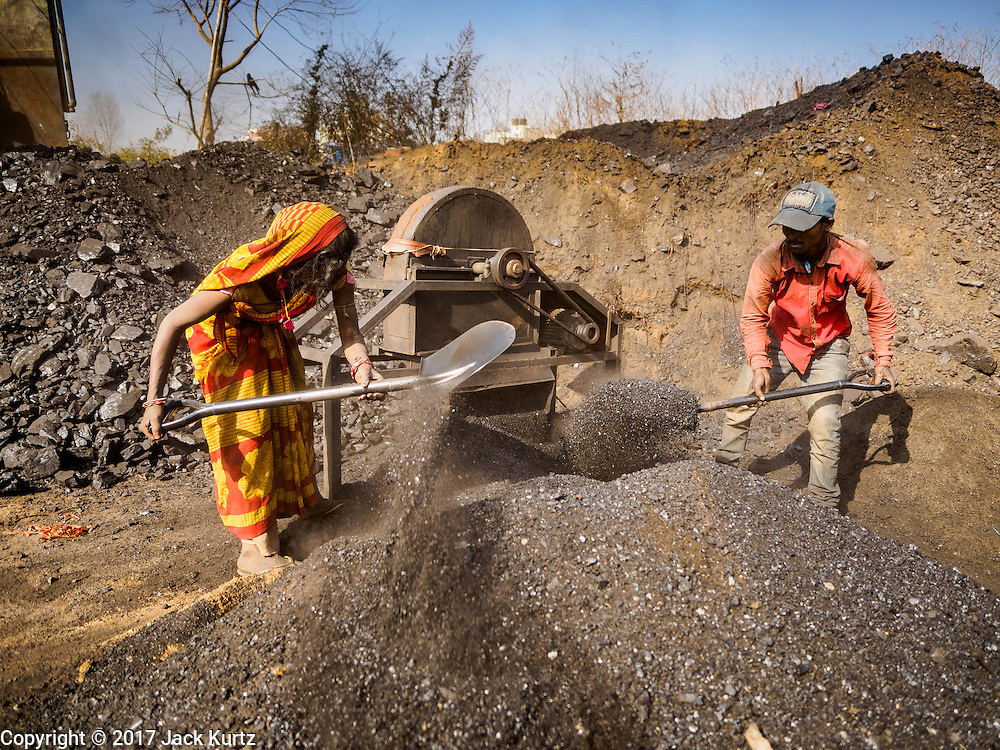 03 MARCH 2017 - BAGMATI, NEPAL: A worker shovel coal dust used to fire the kiln at a brick factory in Bagmati, near Bhaktapur. There are almost 50 brick factories in the valley near Bagmati. The brick makers are very busy making bricks for the reconstruction of Kathmandu, Bhaktapur and other cities in the Kathmandu valley that were badly damaged by the 2015 Nepal Earthquake. The brick factories have been in the Bagmati area for centuries because the local clay is a popular raw material for the bricks. Most of the workers in the brick factories are migrant workers from southern Nepal.       PHOTO BY JACK KURTZ