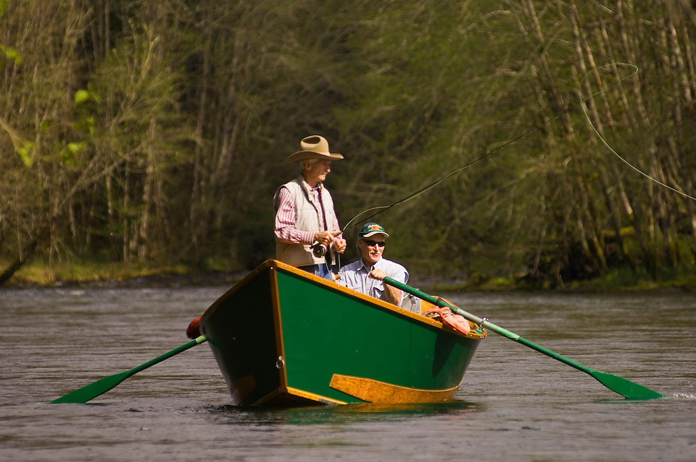 Richard Helfrich and guide Steve Schaefers fly fishing for trout from a drift boat on the McKenzie River, Cascade Mountains, Oregon..
