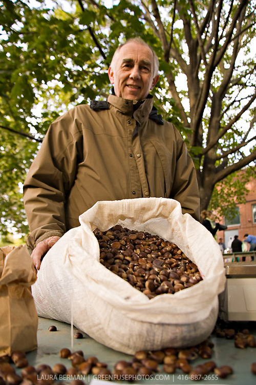 Jonathan Forbes of Forbes Wild Foods  holds a bag of fresh sweet chestnuts at a farmers market.
