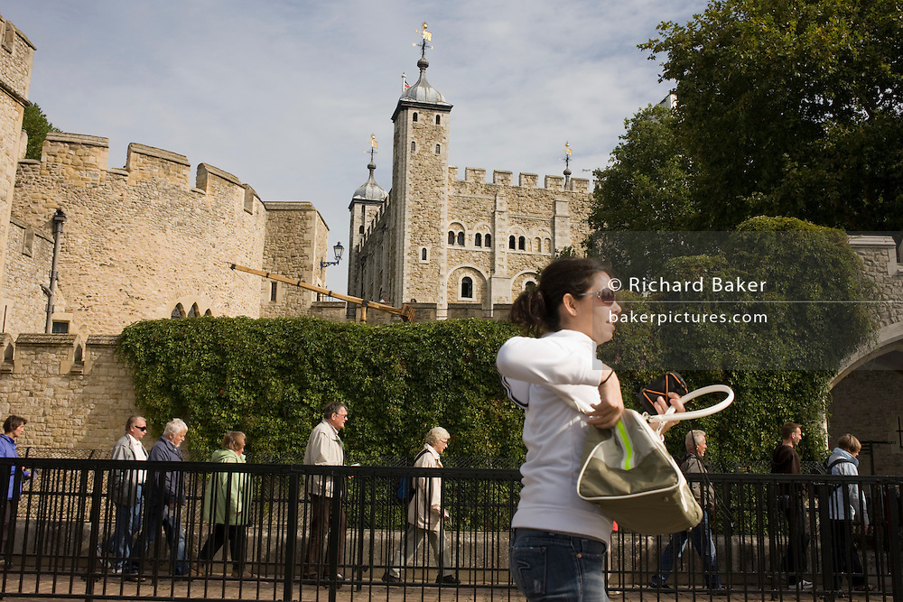 As a smart lady walks past, crowds of tourists walk single-file into the group entrance of the Tower of London.