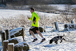 © Licensed to London News Pictures . 23/01/2019. Bolton , UK . A jogger and his dog in Horrocks Wood . Clear skies and snow shrouds the hills in the North West as fog descends over Manchester City Centre . Photo credit : Joel Goodman/LNP