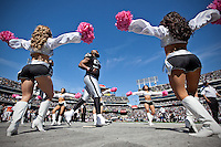 02 October 2011: Defensive tackle (93) Tommy Kelly of the Oakland Raiders runs onto the field past the Raiderettes during player introductions before the New England Patriots 31-19 victory against the Raiders in an NFL football game at O.co Stadium in Oakland, CA.