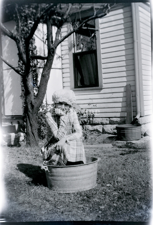 young girl in to small a bathtub outdoors USA 1920s