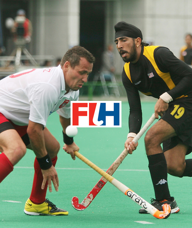 Kakamigahara (Japan): Kevinder Singh of Malaysia being checked by Tomasz Dutkiewick of Poland in the Olympic Hockey Qualifier at Gifu Perfectural Green Stadium at Kakamigahara on 13 April 2008.Malaysia beat Poland 3-0.  Photo: GNN/ Vino John