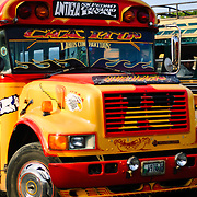 Brightly painted chicken buses in Antigua Guatemala. Usually renovated old American school buses, chicken buses play an essential role in Central American transportation. Famous for its well-preserved Spanish baroque architecture as well as a number of ruins from earthquakes, Antigua Guatemala is a UNESCO World Heritage Site and former capital of Guatemala.