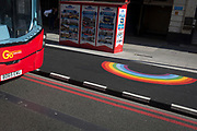 On the day that UK Prime Minster, Boris Johnson announced in parliament of a major easing of Coronavirus pandemic restrictions on July 4th next week - including the re-opening of pubs, restaurants, hotels and hairdressers in England - a London bus is seen stopped in front of double 'Red Route' no parking lines and a rainbow, a symbol of support for NHS and key workers during the pandemic, on 24th June 2020, in London, England. The three month two metre social distance will be also reduced to one metre plus but in the last 24hrs, a further 154 UK covid deaths are reported, bringing the total to 43,081 victims during the Coronavirus pandemic.
