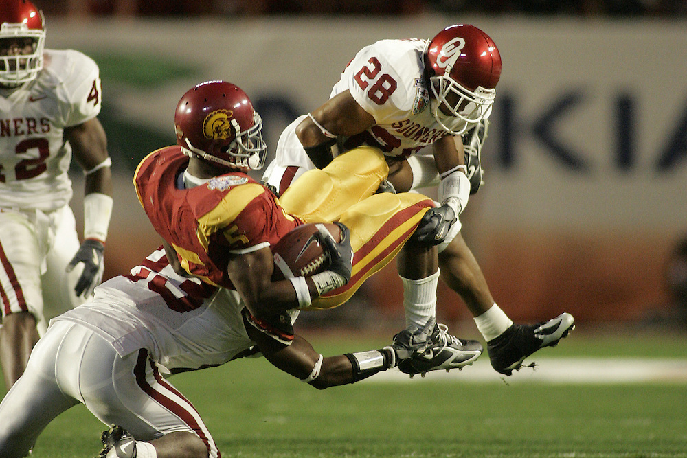 University of Oklahoma defensive backs Anthony Perkins (28) and Brodney Pool (23) upend University of Southern California running back Reggie Bush during USC's 55-19 victory over OU on January 4, 2005 in the FedEx Orange Bowl at Pro Player Stadium in Miami, Florida.