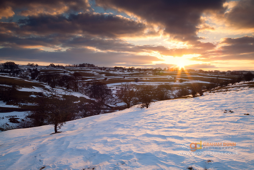 The sun sets over a snow covered Upper Lathkill Dale in the Peak District. Derbyshire, England, UK.