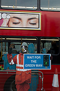 The figure of a construction worker warning pedestrians to cross sensibly, and a passing bus, on 12th December 2017, in London England.