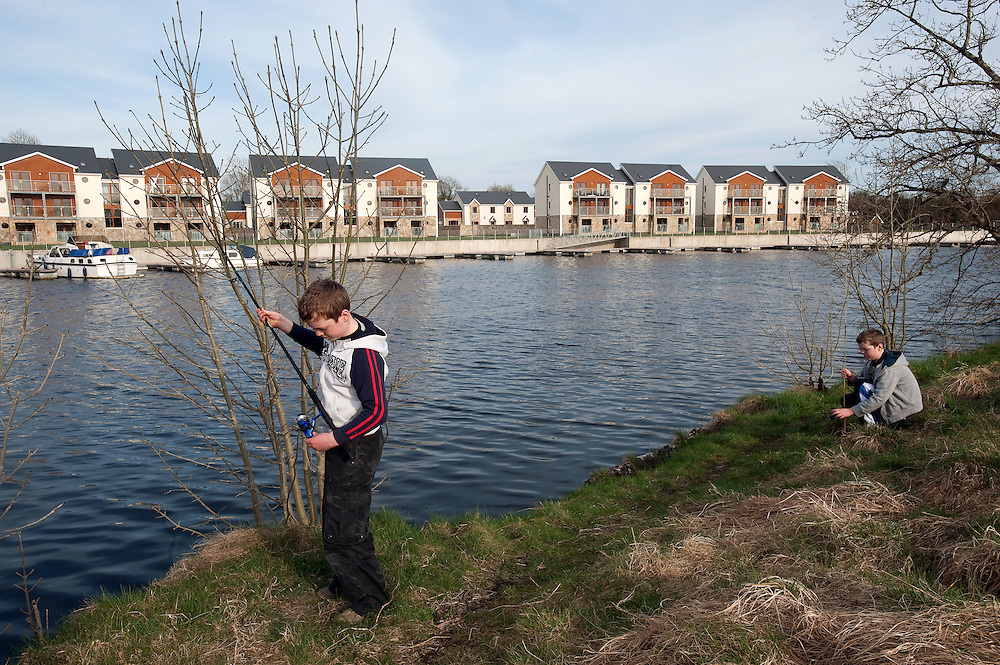 Children fish in the river Shannon, opposite the Shannon Quays development in Roosky, Co Leitrim. The development of 35 houses and 24 apartments is a ghost estate with only one of the houses and a few of the apartments occupied.  The Upper Shannon region enjoyed Section 23 tax incentives which led to an excess amount of properties being built.