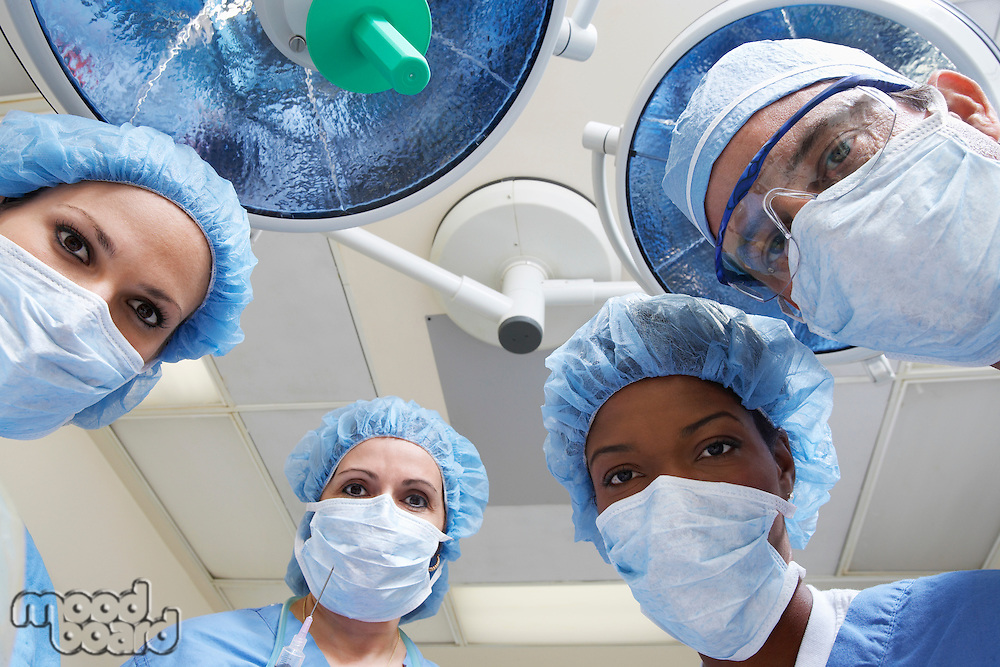 Four surgeons looking down, low angle view