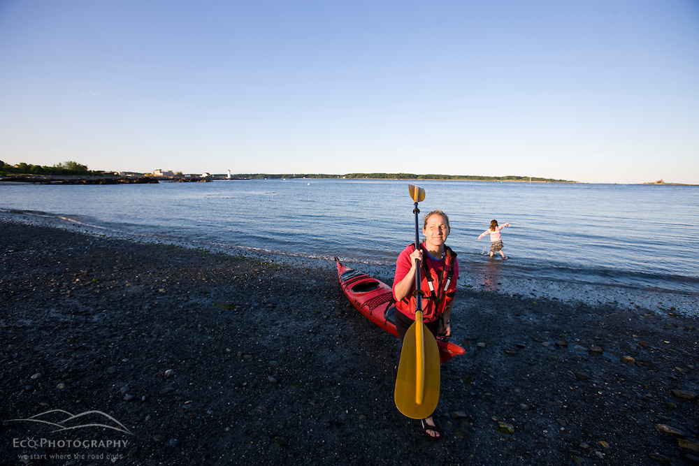 A woman brings her kayak to shore after a paddle in New Castle, New Hampshire.  Her young daughter satnds in the water.