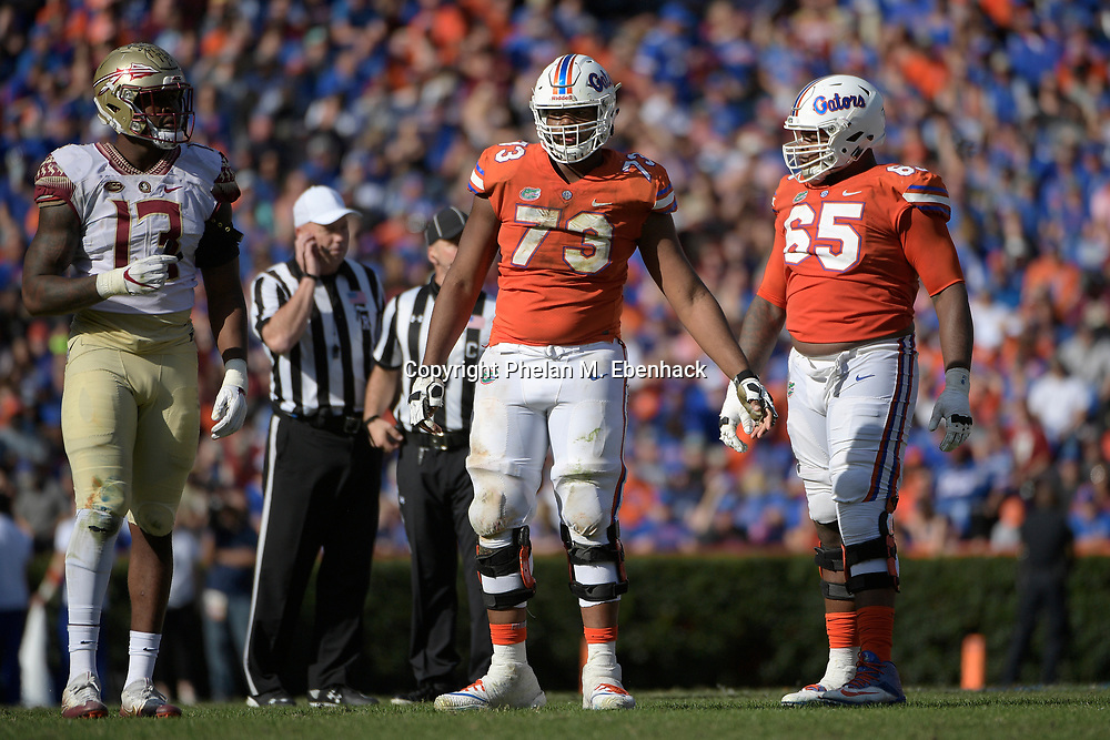 Florida offensive lineman Martez Ivey (73) and offensive lineman Jawaan Taylor (65) line up for a play at the line of scrimmage with Florida State defensive end Joshua Kaindoh (13) during the second half of an NCAA college football game Saturday, Nov. 25, 2017, in Gainesville, Fla. FSU won 38-22. (Photo by Phelan M. Ebenhack)