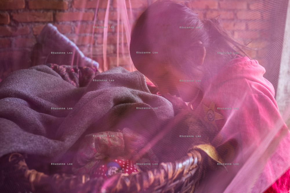Monika (7, in red) talks to her youngest sister Sapana Baniya (2 months) as she lies in a basket in their temporary home in Chautara, Sindhupalchowk, Nepal on 29 June 2015. The three girls lost their mother during the April 25th earthquake that completely levelled their house. Aastha was buried under the rubble together with her mother but Aastha survived. As their father Ratna Baniya (28) cannot care for the children on his own, SOS Childrens Villages has since been supporting the grandmother with financial and social support so that she can manage to raise the children comfortably and ensure that they will all be schooled. Photo by Suzanne Lee for SOS Children's Villages