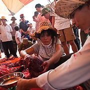 Women sell cuts of prized fighting buffalo meat in Do Son, Vietnam, 27 September, 2009. Do Son, a popular beach-side town three hours east of Hanoi, plays host to an annual Buffalo Fighting Festival every autumn, with water buffalo and their entourage of farmers and trainers arriving from all over the mountainous north, where they have been in isolated training for months. The bulls are led into a football stadium and lock horns, the victor eventually chasing the vanquished out of the grounds to thunderous applauds from thousands of spectators, most of whom are betting heavily on the fights. The buffalo - both winners and losers - are then slaughtered outside the stadium, with their prize-fighting meat fetching up to $50 per kilogram for their owners.