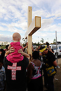 Aurora, CO: 9 month old baby girl Lily McKeel, in pink, rides on her father Ryan's shoulders near a cross erected at impromptu shrine. The group prayed for the 12 killed in the mass theatre shooting rampage.