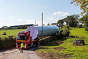 The base of a wind turbine arriving by an exceptional load lorry to Alvington Court Farm, Forest of Dean. Gloucestershire. The truck has rear steering to guide it through small country lanes to arrive at its location ready for construction.