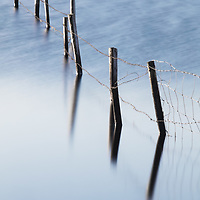 Abandoned fence post reflect in a blue lake.