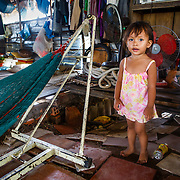 CAPTION: A cafe on built on stilts over the river. In recent years, flooding has damaged the floor, causing it to subside in several places. The girl pictured is the granddaughter of Phan Van Puong. LOCATION: An Binh Ward, Can Tho, Vietnam. INDIVIDUAL(S) PHOTOGRAPHED: Phan Thi Minh Thu.