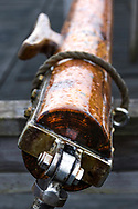 up close photography of a wooden mast for a Sail boat, tied to the storage with a rope