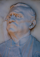 Close-up of a bas relief of a bespectacled man on a grave in Isola San Michel in Venice, Italy.
