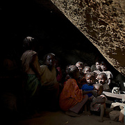 Nuba children take cover from possible bombardments by Sudan's Army Forces airplane, in a cave outside Buram village.