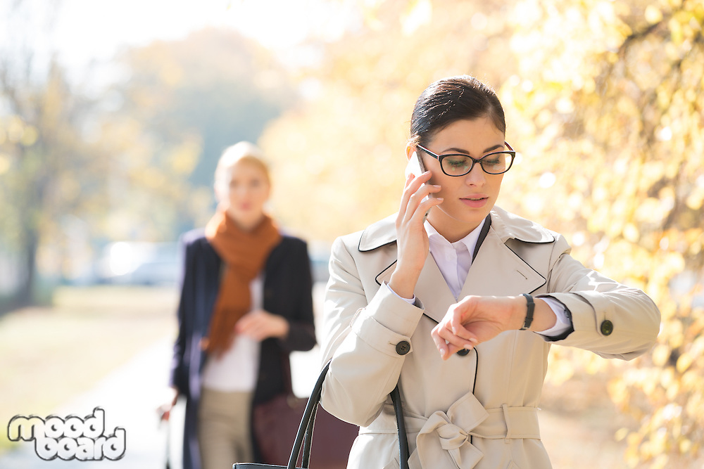 Businesswoman checking time while colleague standing in background at park