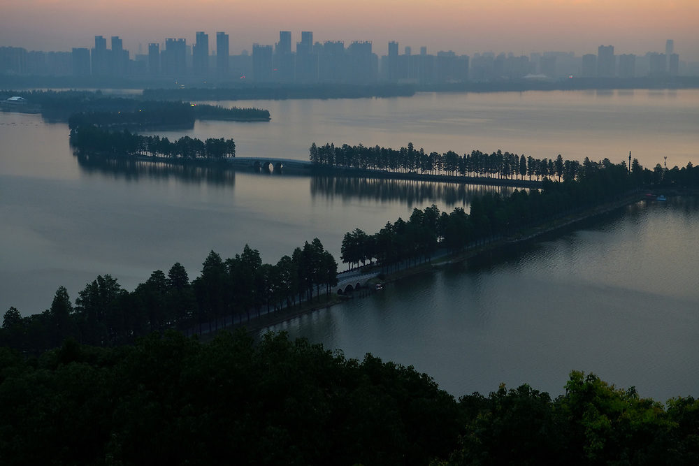 Landscape shot of the East Lake Greenway park, with the Wuhan skyline behind, Hubei, China