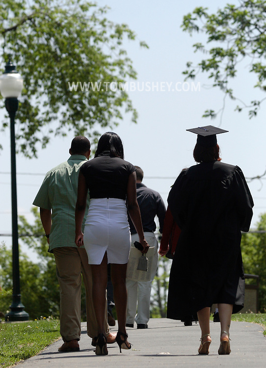 Middletown - A group of people, including on graduate at right, walk away after the 58th commencement at Orange County Community College on May 17, 2008.