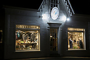 Fisherman's Daughter clapboard store and window displays illuminated at night in High Street Chatham, Cape Cod New England, USA