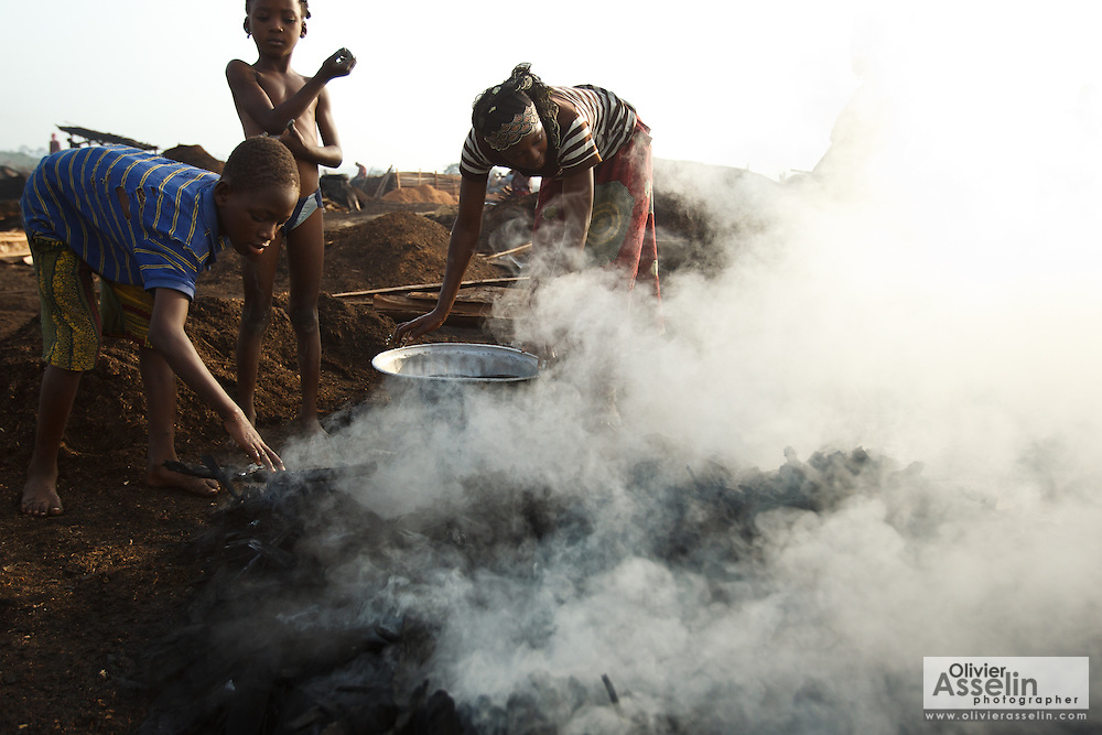 A woman and children splash water on hot charcoal to cool it off at a wood charcoal production site on the outskirts of San Pedro, Bas-Sassandra region, Côte d'Ivoire on Sunday March 4, 2012. Men, women and children - who don't go to school - work here seven days a week.