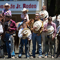 Cowboys and cowgirls competing in the 63rd Annual Woodside Junior Rodeo remove their hats during the national anthem.