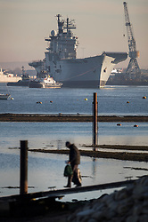 © Licensed to London News Pictures. 1/12/2016. Portsmouth, UK. A man walks down a ramp as tugs move the former Royal Navy aircraft carrier HMS Illustrious from Portsmouth Naval Base out into the harbour ahead of her final voyage to a scrap yard.  Illustrious, the last of the Invincible Class carriers, has been sold to the Leyal Ship Recycling and Dismantling company in Aliaga, Turkey - the same yard that dismantled her sister ships Ark Royal and Invincible. Photo credit: Peter Macdiarmid/LNP