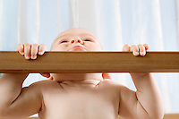 Infant child holding himself up in wooden cot
