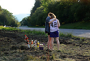 Two young women embrace after leaving a rose wreath at the site of the fatal car crash that killed seven along Route 13 in Truxton, NY, Thursday, May 30, 2013. Four children and three adults were killed when their minivan was hit by a trailer that became disconnected from it's hitch. The trailer slammed into a minivan with eight people inside. Four children under the age of 10 and three adults in their early 20s were killed. One man survived the crash. <br /> (AP photos/Heather Ainsworth)