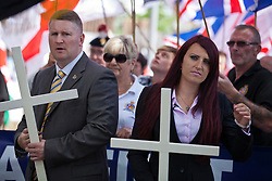 Luton, UK. 27th June, 2015. Britain First's leader Paul Golding and deputy leader Jayda Fransen lead supporters of the far-right group on a march through Luton. Police failed to prevent the leaders from attending the march, but ensured that they could not carry banners demanding no more mosques. A counter-protest was organised by Unite Against Fascism.