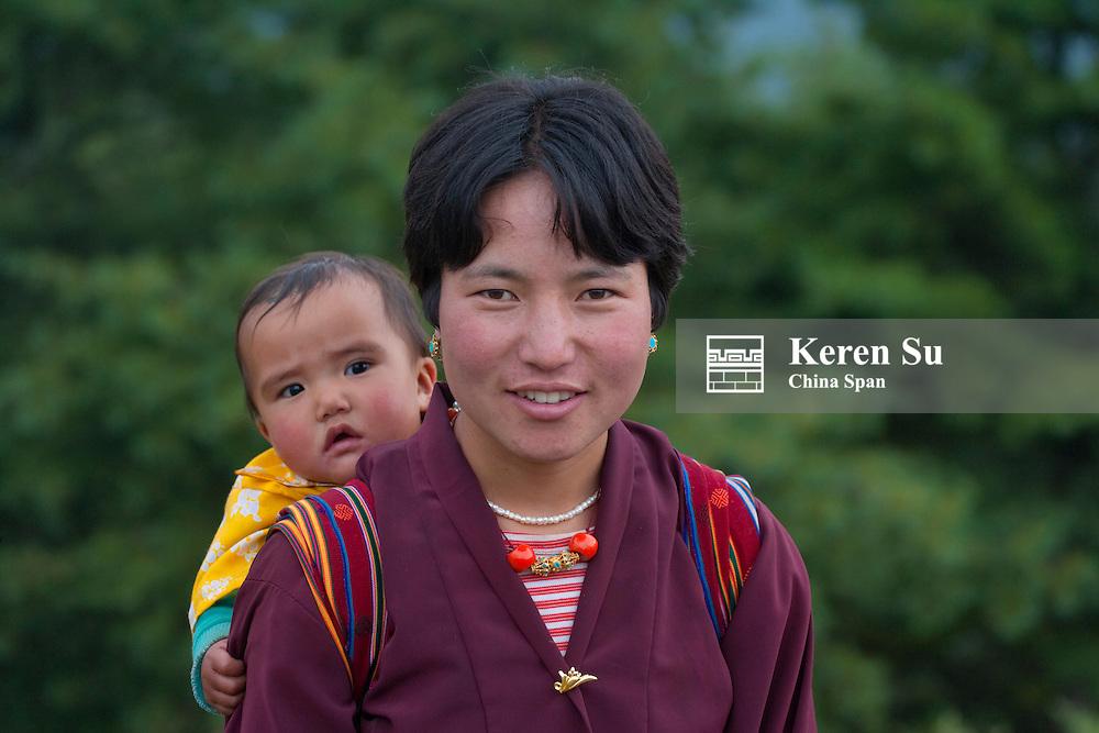 Mother carrying baby on back, Gangtey village, Bhutan