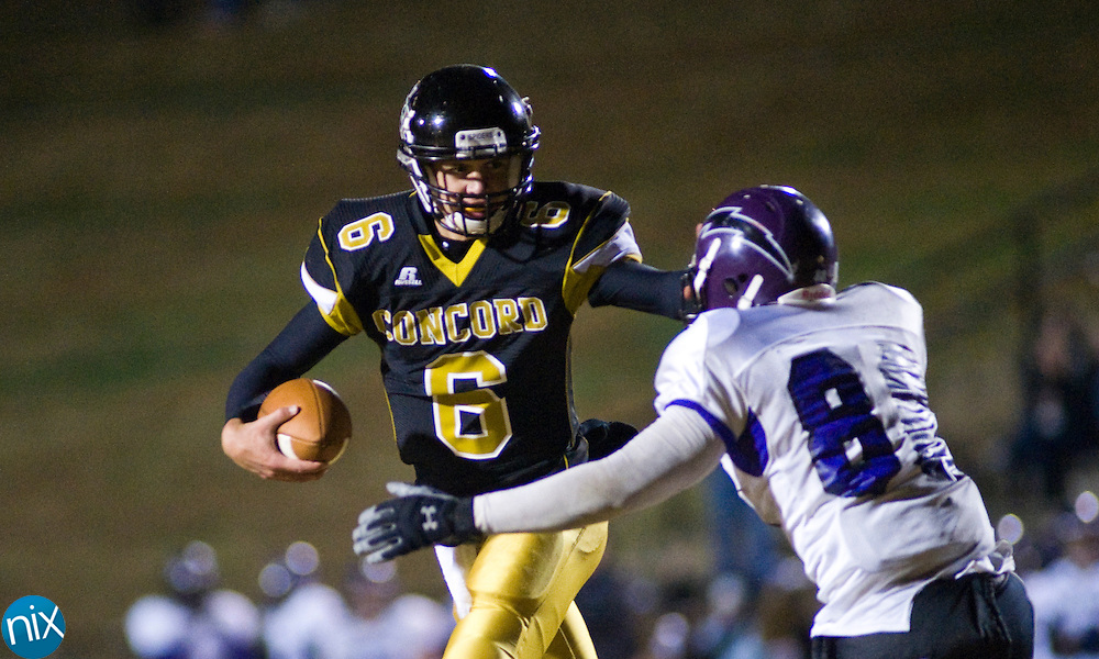 Concord quarterback B.J. Beecher tries to get past Cox Mill's Tristian Green during the first round of the NCHSAA 3A playoffs Friday night at Concord High School. Concord won the game 30-12 to advance. (Photo by James Nix)