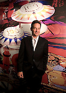 "corporate portraits on location,by miami photographer,matthew pace, of David Young holding mini pinball in front of mural,""100 poimts when lit"" in his office."