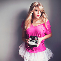 Young woman with blonde hair wearing a pink shirt and short lace skirt holding an Poloroid camera