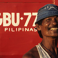 Philippines, Longshoreman at ferry port along the waterfront in Dumaguete City in Negros Oriental Province