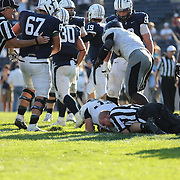 A referee makes a tackle after play had been stopped during the Yale V Army, Football match at Yale Bowl, New Haven. Yale won the match 49-43 in overtime in front of a crowd of 34,142. New Haven, Connecticut, USA. 27th September 2014. Photo Tim Clayton