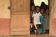 Children look through a doorway at the Nyologu Primary School in the village of Nyologu, northern Ghana, on Wednesday June 6, 2007.