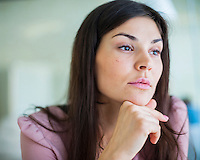 Thoughtful young businesswoman looking away in office