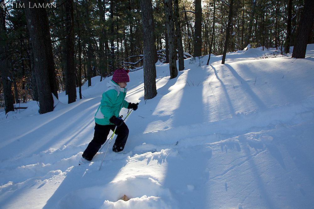 Jessica Laman (age 9) cross country skiing in the woods.