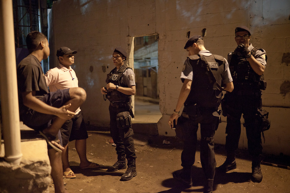 Police Pacification Unit (UPP) officer XXX Pinheiro, left, and her patrol group, check ID's in Complexo do Caju, a complex of a newly pacified favelas in the North Zone, Rio de Janeiro, Brazil, on Saturday, April 27, 2013. <br />