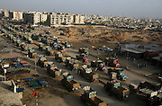 Trucks loaded with sand drive through a predominately Pukhtun residential area near Shorab Goth in Karachi, Pakistan.
