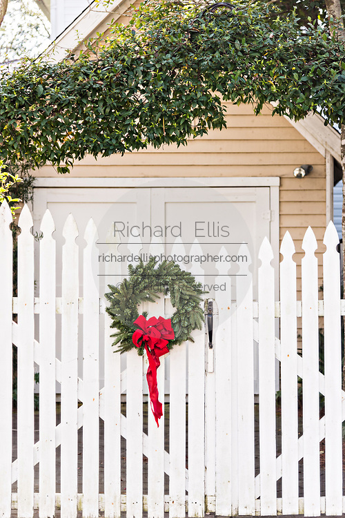 A wooden picket fence of a historic home decorated with a Christmas wreath on Water Street in Charleston, SC.